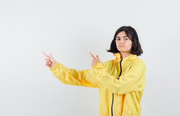 Młoda dziewczyna w żółtej bomberce i różowej spódnicy, wskazując palcami wskazującymi w lewo i patrząc poważnie