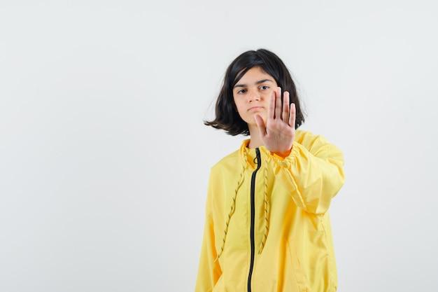 Młoda dziewczyna w żółtej bomberce pokazuje znak stopu i wygląda poważnie