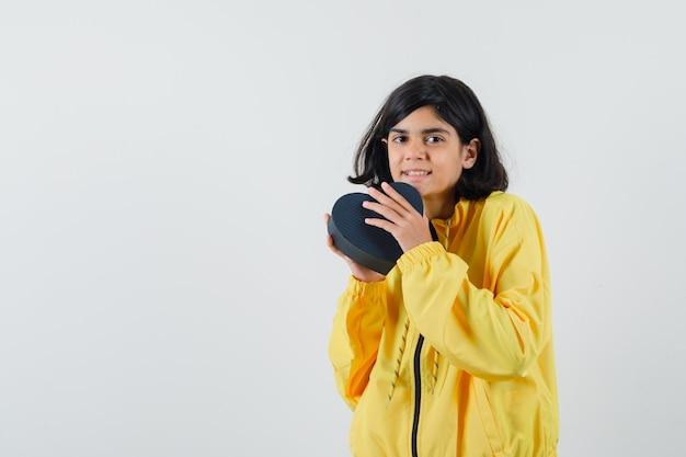 Młoda dziewczyna w żółtej bomberki trzyma pudełko i wygląda szczęśliwy