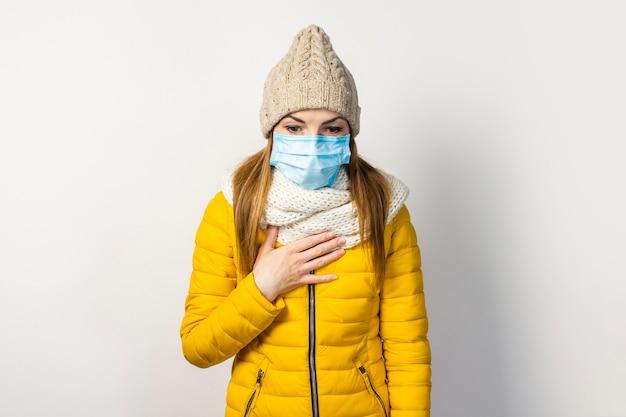 Młoda dziewczyna w żółtej kurtce i kapeluszu z maską medyczną na twarzy, trzymając rękę na piersi i kaszląc