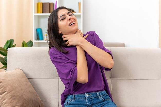 Młoda dziewczyna w zwykłych ubraniach, dławiąca się, trzymająca się za ręce na szyi w panice, siedząca na kanapie w jasnym salonie