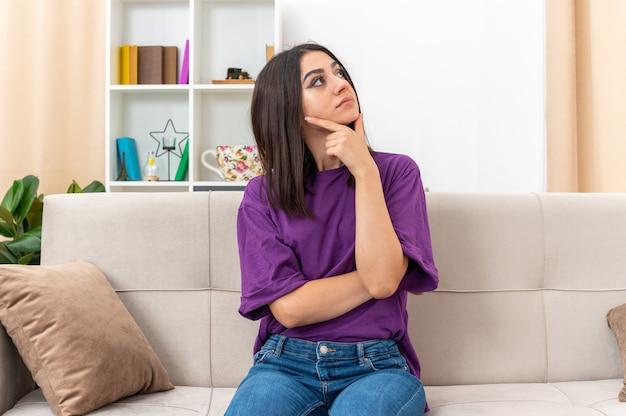 Młoda dziewczyna w zwykłych ubraniach, patrząca na bok z ręką na brodzie z zamyślonym wyrazem twarzy, siedząca na kanapie w jasnym salonie