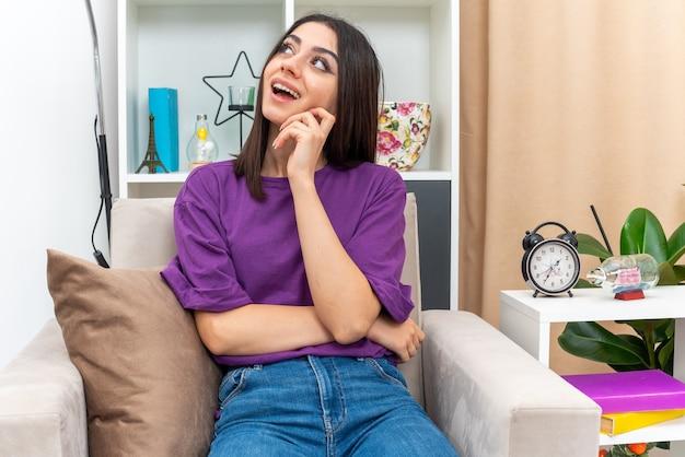 Młoda dziewczyna w zwykłych ubraniach patrząca w górę z zamyślonym wyrazem twarzy myśląca pozytywnie siedząc na krześle w jasnym salonie