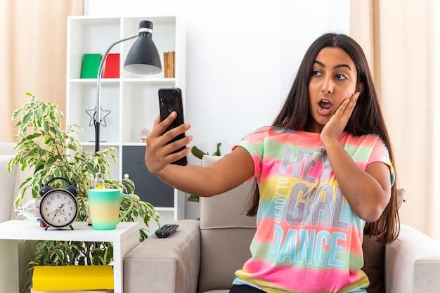 Młoda dziewczyna w zwykłych ubraniach robi selfie za pomocą smartfona, siedząc na krześle w jasnym salonie