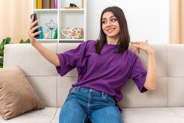 Młoda dziewczyna w zwykłych ubraniach robi selfie za pomocą smartfona, uśmiechając się pewnie, siedząc na kanapie w jasnym salonie