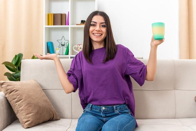 Młoda dziewczyna w zwykłych ubraniach trzyma filiżankę herbaty uśmiechając się radośnie, prezentując coś z ręką, siedząc na kanapie w jasnym salonie