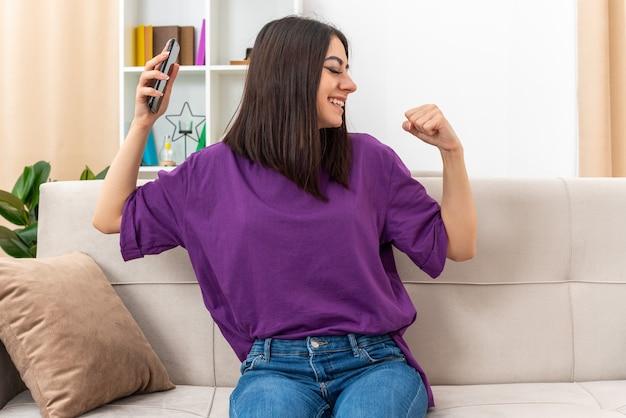 Młoda dziewczyna w zwykłych ubraniach trzyma smartfona zaciskając pięść szczęśliwa i podekscytowana, ciesząc się swoim sukcesem, siedząc na kanapie w jasnym salonie