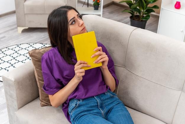 Młoda dziewczyna w zwykłych ubraniach trzymająca książkę patrząca na bok zdziwiona siedząca na kanapie w jasnym salonie