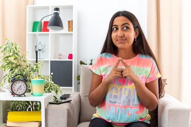 Młoda dziewczyna w zwykłych ubraniach trzymająca się za ręce, patrząca na bok, chytrze uśmiechając się, czekając na coś siedzącego na krześle w jasnym salonie