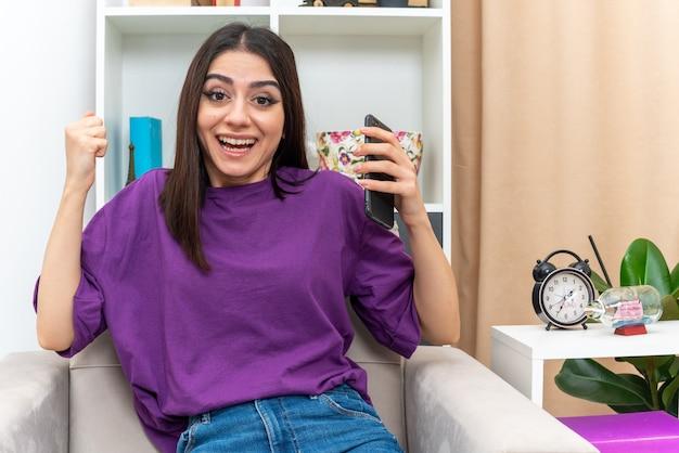 Młoda dziewczyna w zwykłych ubraniach trzymająca smartfona wygląda na szczęśliwą i podekscytowaną zaciskającą pięść, siedzącą na krześle w jasnym salonie