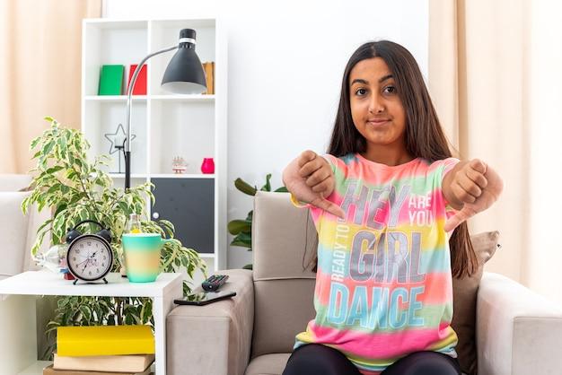 Młoda dziewczyna w zwykłych ubraniach uśmiecha się pewnie pokazując kciuk w dół, siedząc na krześle w jasnym salonie