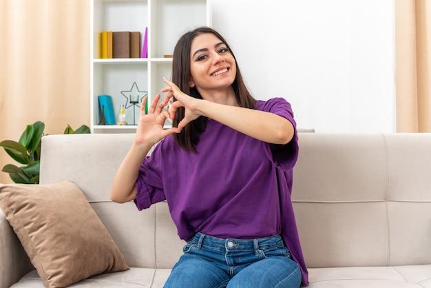 Młoda dziewczyna w zwykłych ubraniach wygląda na szczęśliwą i pozytywnie uśmiecha się radośnie wykonując gest serca palcami siedzącymi na kanapie w jasnym salonie