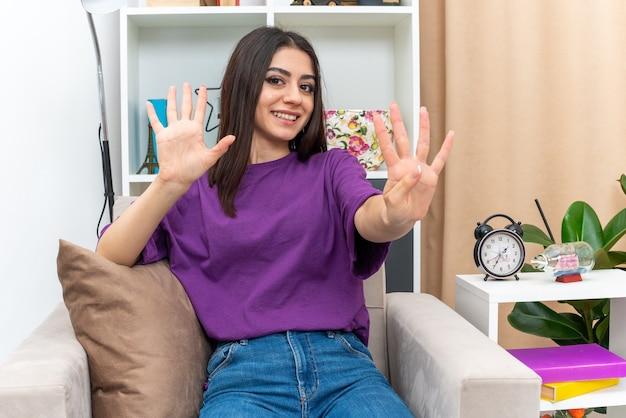 Młoda dziewczyna w zwykłych ubraniach wygląda na szczęśliwą i pozytywnie uśmiechniętą pokazując numer dziewięć siedzący na krześle w jasnym salonie