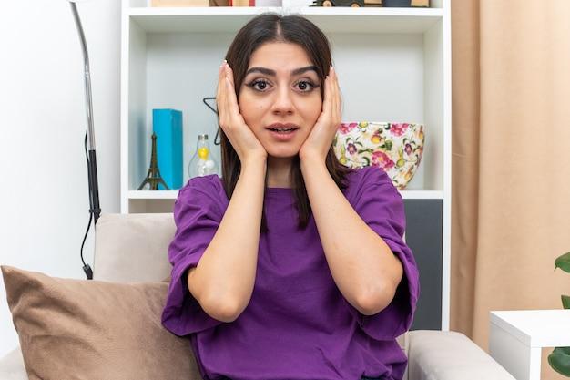 Młoda dziewczyna w zwykłych ubraniach wygląda na zdziwioną i zaskoczoną siedzącą na krześle w jasnym salonie