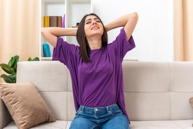 Młoda dziewczyna w zwykłych ubraniach wygląda na zirytowaną i zirytowaną z rękami na głowie, siedząc na kanapie w jasnym salonie