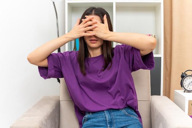 Młoda dziewczyna w zwykłych ubraniach zakrywających oczy dłońmi, siedząca na krześle w jasnym salonie
