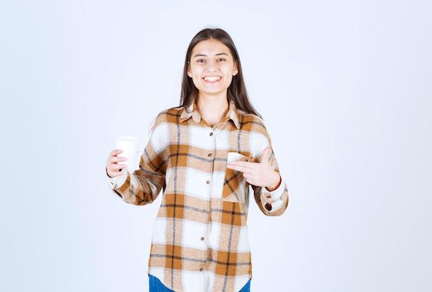 Młoda dziewczyna, wskazując na filiżankę herbaty na białej ścianie.