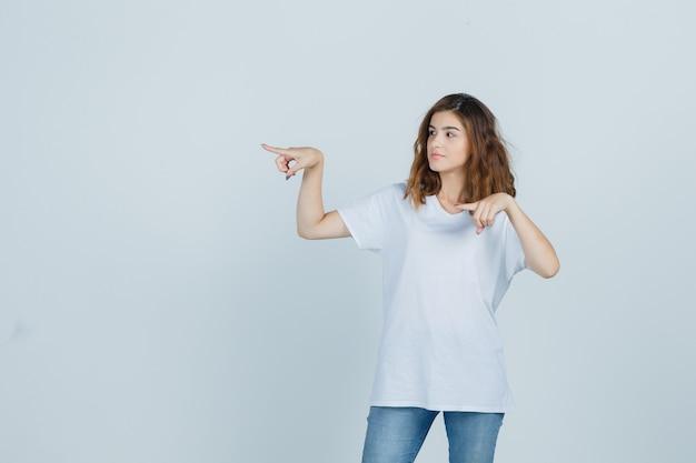 Młoda dziewczyna, wskazując na lewą stronę w t-shirt, dżinsy i pewny siebie, widok z przodu.