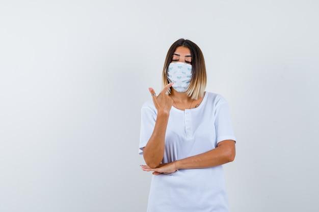 Młoda dziewczyna, wskazując na siebie palcem wskazującym, trzymając dłoń pod łokciem w białej koszulce, masce i patrząc poważnie, widok z przodu.