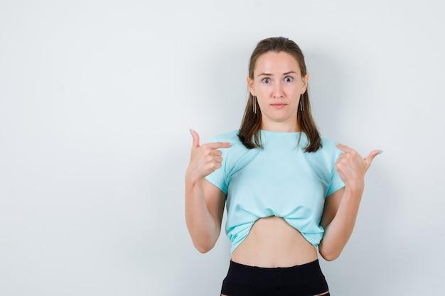 Młoda dziewczyna wskazując na siebie w turkusowej koszulce, spodniach i patrząc zszokowana, widok z przodu.