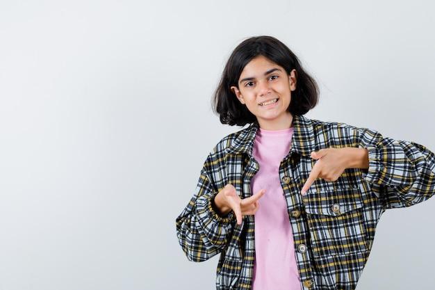 Młoda dziewczyna wskazując palcem w dół w kraciastą koszulę i różowy t-shirt i wygląda ładnie, widok z przodu.