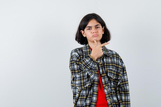 Młoda dziewczyna wskazując palcem w prawo w kraciastej koszuli i czerwonej koszulce i patrząc poważnie. przedni widok.