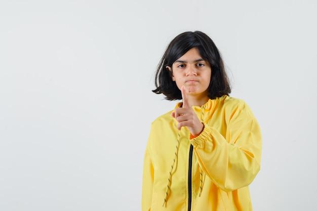 Młoda dziewczyna, wskazując palcem wskazującym na aparat w żółtej bomber jacket i patrząc poważnie