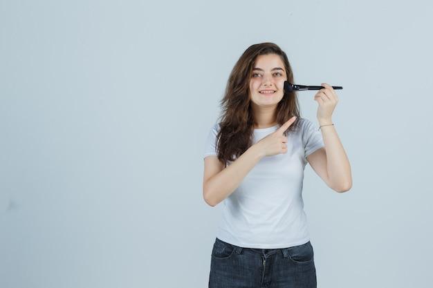 Młoda dziewczyna wskazując pędzel do makijażu w t-shirt, dżinsy i ładny wygląd. przedni widok.