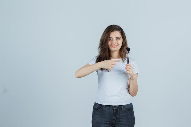 Młoda dziewczyna wskazując pędzel do makijażu w t-shirt, dżinsy i patrząc pewnie, widok z przodu.