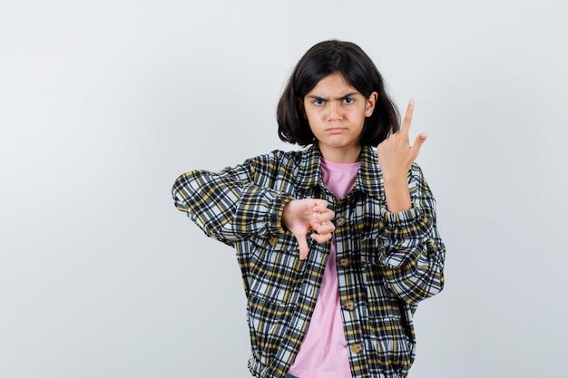 Młoda dziewczyna wskazując w górę i pokazując kciuk w dół w kraciastej koszuli i różowym t-shirt i patrząc niezadowolony. przedni widok.