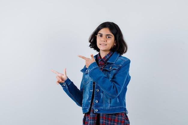 Młoda dziewczyna wskazując w lewo palcami wskazującymi w kraciastej koszuli i dżinsowej kurtce i patrząc ładny, widok z przodu.