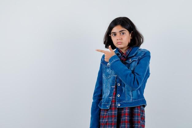 Młoda dziewczyna wskazując w lewo palcem wskazującym w kraciastej koszuli i dżinsowej kurtce i patrząc poważnie, widok z przodu.