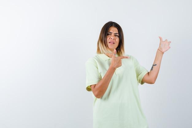 Młoda dziewczyna, wskazując w prawo w koszulce i patrząc poważnie. przedni widok.