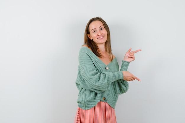 Młoda dziewczyna, wskazując w prawo z palcami wskazującymi w dzianinie, spódnicy i patrząc szczęśliwy. przedni widok.