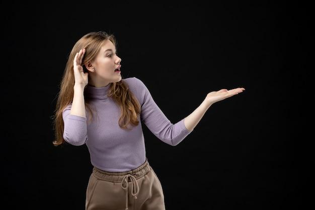 Młoda dziewczyna wskazująca coś na lewą stronę i uważnie słuchająca w ciemności