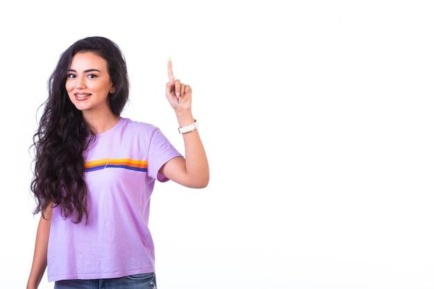 Młoda dziewczyna wskazująca kierunek do góry.
