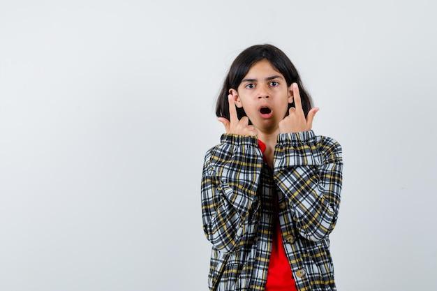 Młoda dziewczyna wskazująca w górę podczas otwierania ust w kraciastej koszuli i czerwonej koszulce i patrząc zdziwiona, widok z przodu.
