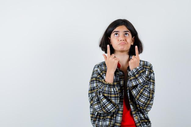 Młoda dziewczyna wskazuje palcem wskazującym w górę, patrząc powyżej w kraciastej koszuli i czerwonej koszulce i patrząc poważnie, widok z przodu.