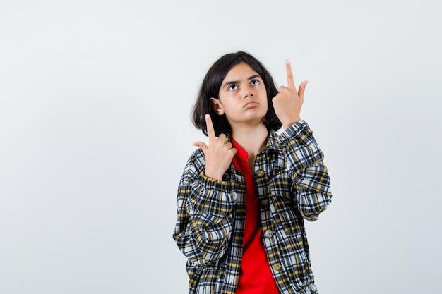 Młoda dziewczyna wskazuje w kraciastą koszulę i czerwoną koszulkę i wygląda na skupioną. przedni widok.