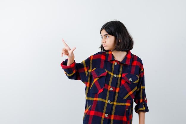 Młoda dziewczyna wskazuje w kraciaste koszule i wygląda ładny, widok z przodu.