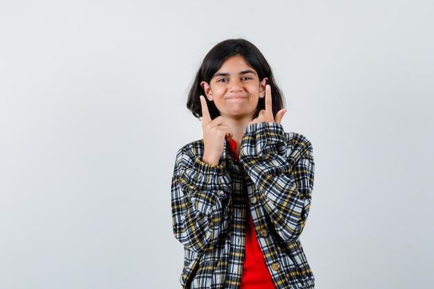 Młoda dziewczyna wskazuje w kratkę koszulę i czerwoną koszulkę i wygląda na szczęśliwą. przedni widok.