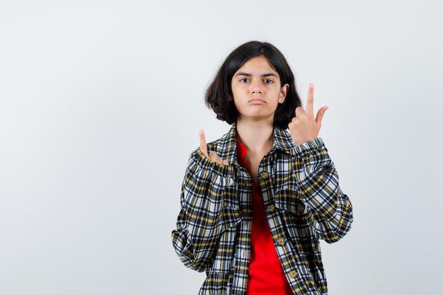 Młoda dziewczyna wskazuje w kratkę koszulę i czerwoną koszulkę i wygląda poważnie, widok z przodu.