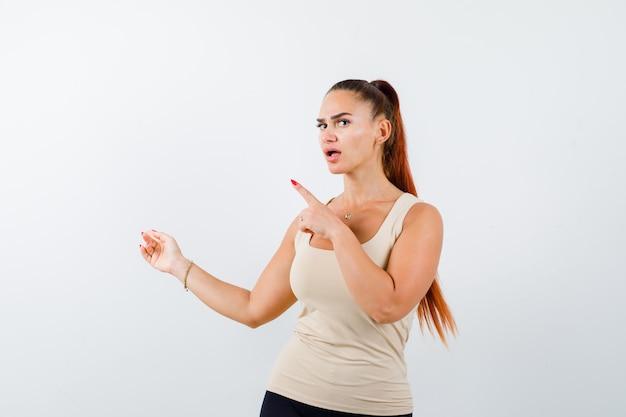 Młoda dziewczyna wskazuje w lewo z palcami wskazującymi w beżowym topie, czarnych spodniach i wygląda na zaskoczoną