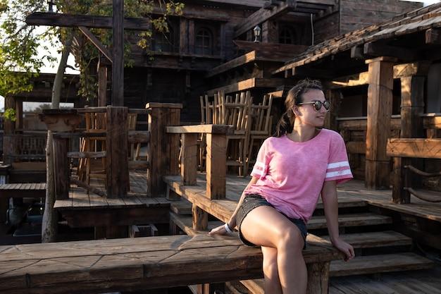 Młoda dziewczyna wśród drewnianych detali dużego domu.