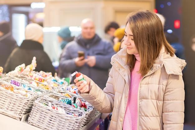 Młoda dziewczyna wybiera prezenty, pamiątki na jarmarku bożonarodzeniowym