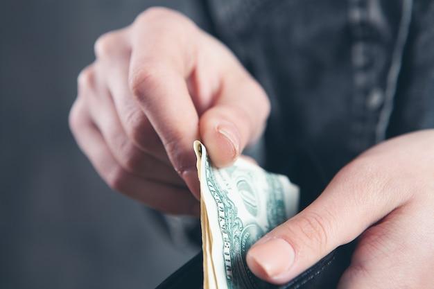 Młoda dziewczyna wyciąga banknoty z portfela