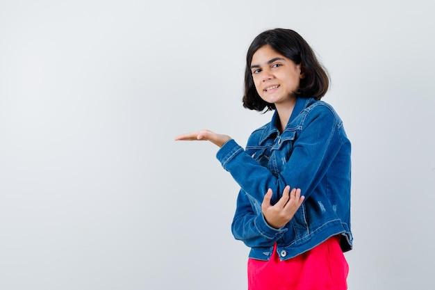 Młoda dziewczyna wyciąga jedną rękę trzymając coś i trzymając rękę na łokciu w czerwonej koszulce i dżinsowej kurtce i wygląda na szczęśliwą, widok z przodu.