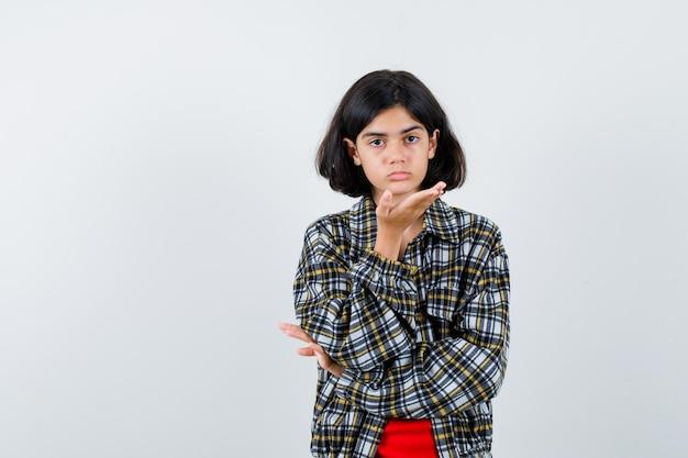 Młoda dziewczyna wyciąga ręce trzymając coś w kraciastej koszuli i czerwonej koszulce i wygląda ładnie. przedni widok.