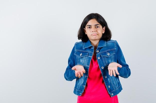 Młoda dziewczyna wyciąga ręce w pytający sposób w czerwonej koszulce i dżinsowej kurtce i wygląda na zakłopotaną