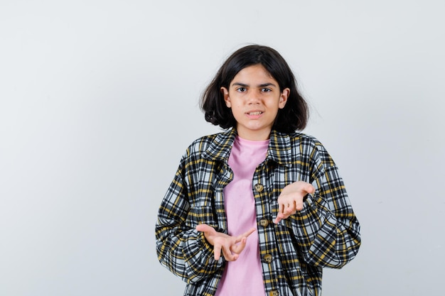 Młoda dziewczyna wyciąga ręce w pytający sposób w kraciastej koszuli i różowej koszulce i wygląda na zakłopotaną. przedni widok.